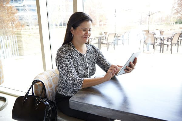 Smiling lady using her Ipad to check messages