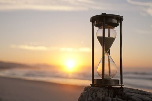 Hourglass with beach sunset in background