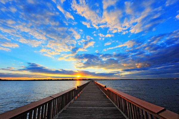 A beautiful sun setting with a dock.