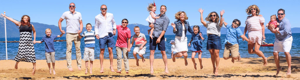 Fritch Family jumping for a beach photo.